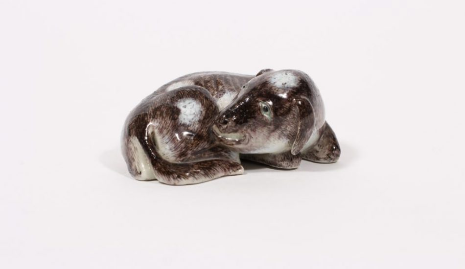 A finely glazed figure of a recumbent dog with incised red mark (Qing dynasty, 18th/19th century)