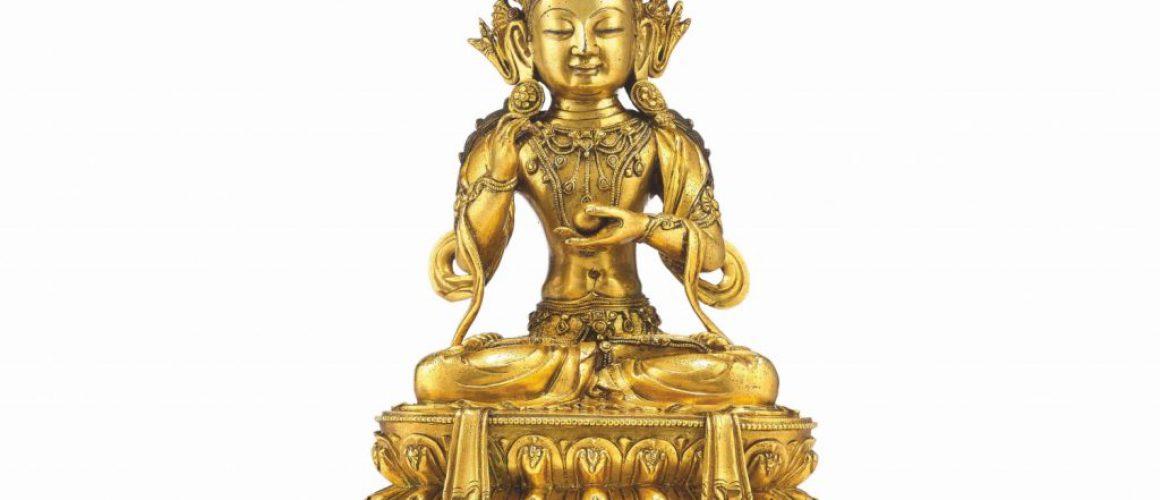 558 - A gilt copper alloy seated figure of Avalokitesvara/Guanyin