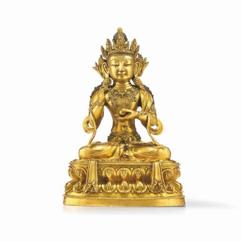 558 - A gilt copper alloy seated figure of Avalokitesvara/Guanyin