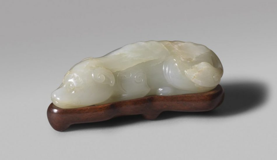 A pale celadon jade carving of a recumbent dog with fitted wood stand (Song/early Yuan dynasty)